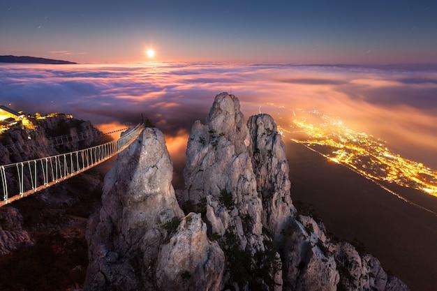 Piękny nocny krajobraz z pełni księżyca, morza, skał i niskich chmur