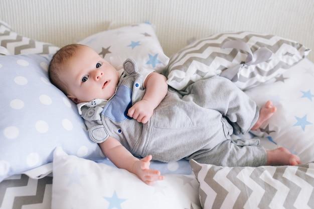 Piękny noworodek leżący w poduszkach w delikatnych odcieniach szarości, błękitu i bieli