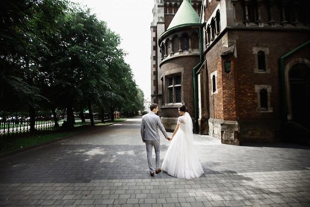 Piękny nowożeńcy pary spacer blisko starego kościół chrześcijańskiego
