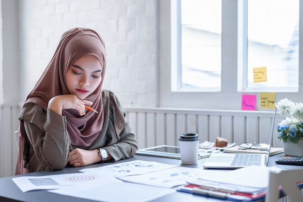 Piękny nowożytny arabski biznesowej kobiety brązu hidżab dyskutuje dane planowania finansowego w kreatywnie miejscu pracy.
