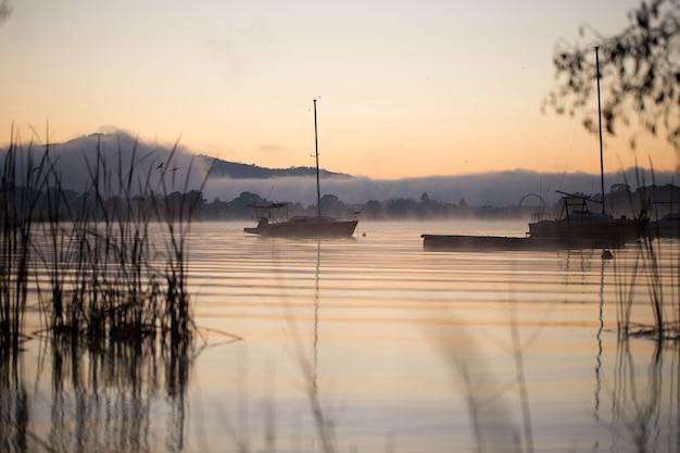 Piękny obraz hipnotyzującego zachodu słońca odbijającego się w wodzie na tle gór