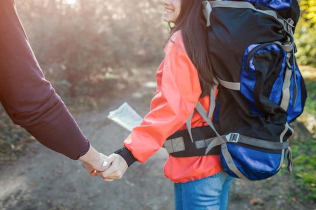 Piękny obraz młodego mężczyzny i kobiety, trzymając się za ręce razem. ma plecak z tyłu i mapę na rękach. idą razem.