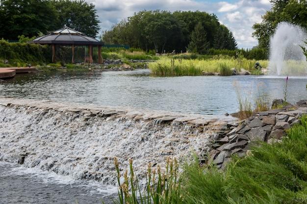 Piękny obraz na kaskadzie wody wypływającej ze stawu w parku