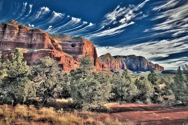 Piękny obraz pomarańczowych skalistych wzgórz i drzew liściastych pod wielkim niebem w ciągu dnia w sedonie