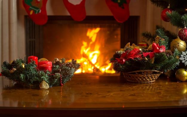 Piękny obraz stołu z bożonarodzeniowym wieńcem przed płonącym kominkiem i ozdobioną choinką. puste miejsce na tekst.