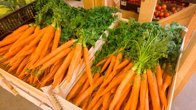 Piękny obraz świeżej organicznej marchwi z gmo w drewnianej skrzyni w sklepie warzywnym. zbliżenie tekstury lub wzór świeżych dojrzałych warzyw. piękne tło żywności