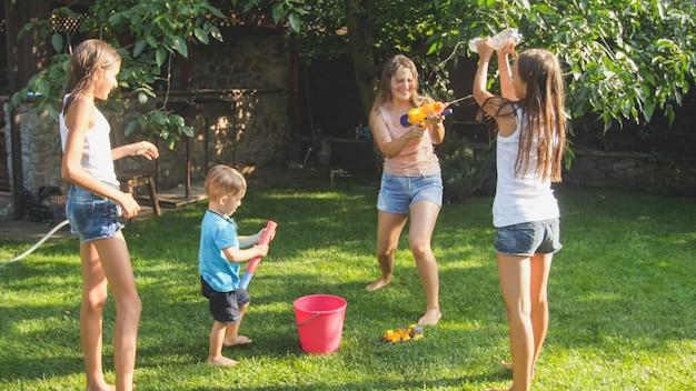 Piękny obraz szczęśliwej roześmianej rodziny z dziećmi bawiącymi się w upalny letni dzień z pistoletami na wodę i wężem ogrodowym. rodzinna zabawa i zabawa na świeżym powietrzu latem