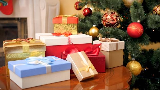 Piękny obraz wielu prezentów i prezentów na boże narodzenie leżącego na drewnianym stole w salonie domu przed girlandami i bombkami chrismtas