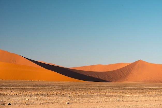 Piękny obraz wydm parku narodowego namib na tle gór z brązowym piaskiem