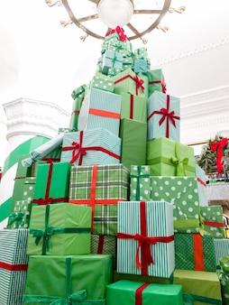 Piękny obraz wysokiej choinki z pudełek z świątecznymi prezentami
