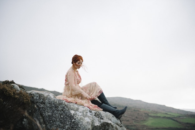 Piękny obrazek przedstawiający rudą suczkę o czystej białej skórze w różowej sukni