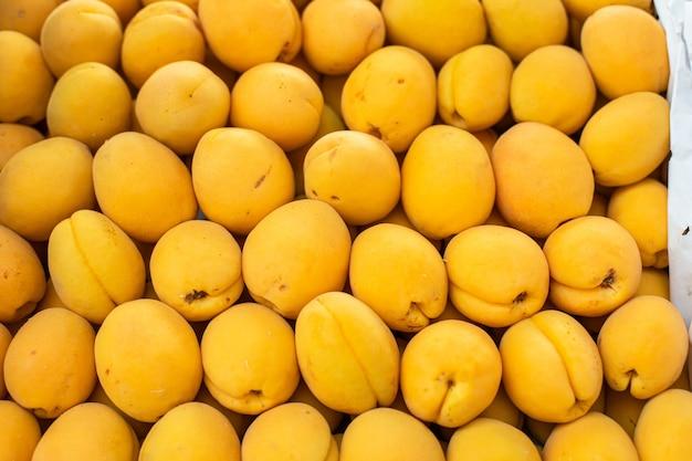Piękny obrazek z dużą, świeżą, żółtą morelą sprzedawaną na rynku.