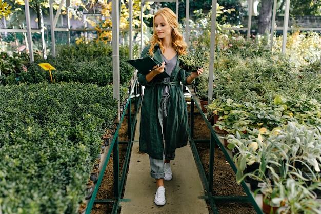 Piękny ogród botaniczny, pełen zielonych kwiatów i krzewów. dziewczyna o blond kręconych włosach, pozuje, przedstawiając się jako biolog.