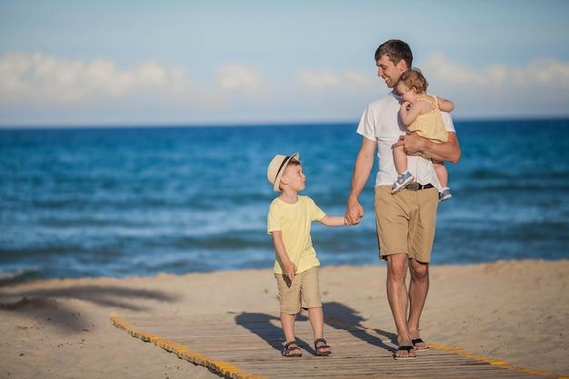 Piękny ojciec z dwójką dzieci spacerujących po plaży w pobliżu morza.