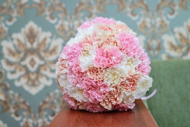 Piękny okrągły bukiet ślubny z białych i różowych goździków na stole