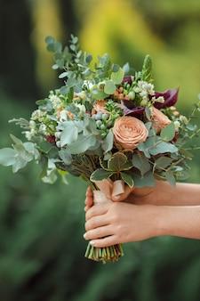 Piękny oryginalny bukiet ślubny w rękach panny młodej