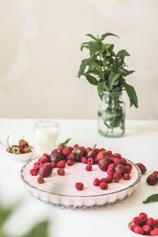 Piękny pachnący kremowy placek z malinami, truskawkami i miętą w szklanym naczyniu na zboczu.