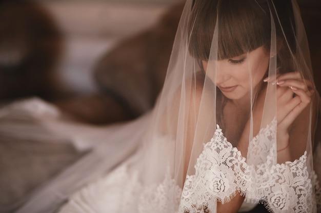 Piękny panny młodej kobiety portret w biel sukni. fashion beauty girl. makijaż. biżuteria. wypielęgnowane paznokcie. ślubna dziewczyna w luksusowej ślubnej sukni