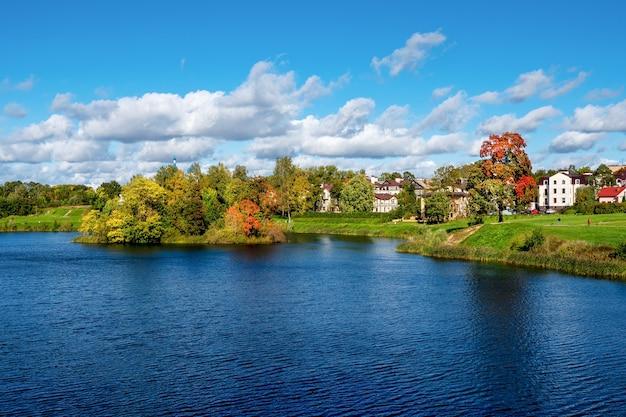 Piękny panoramiczny jesienny krajobraz z jasnymi drzewami nad brzegiem jeziora