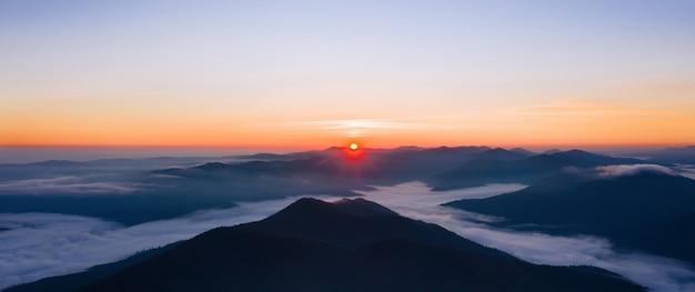 Piękny panoramiczny krajobraz mglistych gór o wschodzie słońca