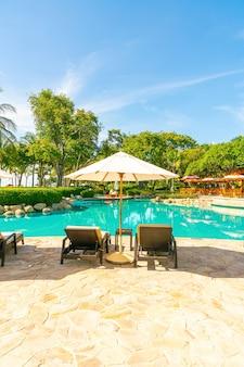 Piękny parasol i krzesło wokół basenu w hotelu i ośrodku - koncepcja wakacji