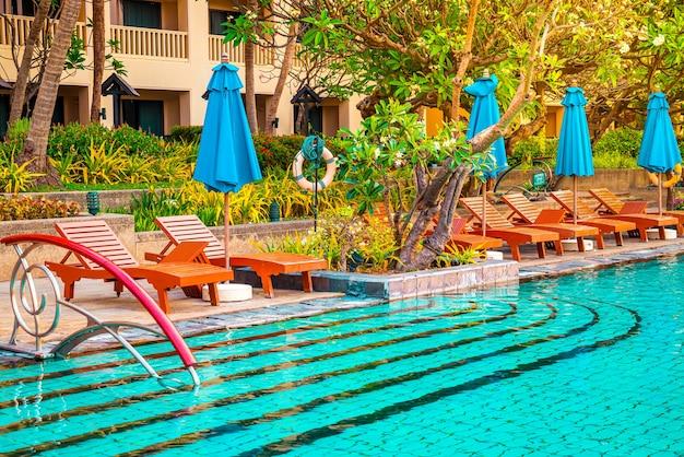 Piękny parasol i krzesło wokół basenu w hotelu i ośrodku - koncert wakacyjny i wakacyjny