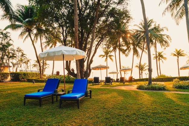 Piękny parasol i krzesło wokół basenu w hotelu i ośrodku wypoczynkowym - koncert wakacyjny i wakacyjny