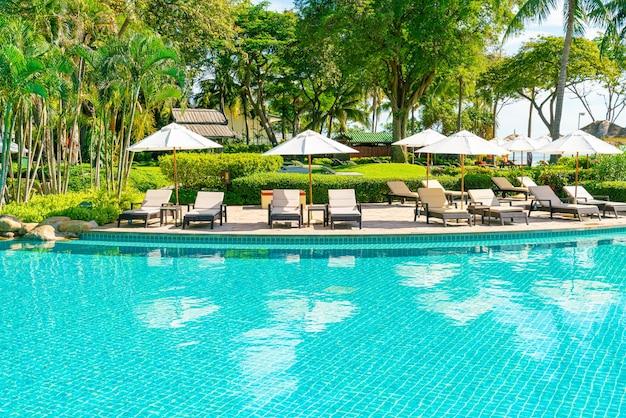 Piękny parasol i krzesło wokół basenu w hotelu i ośrodku