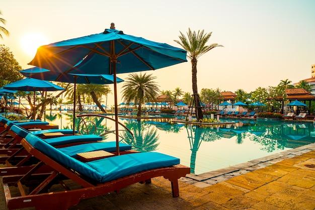 Piękny parasol i krzesło wokół basenu w hotelu