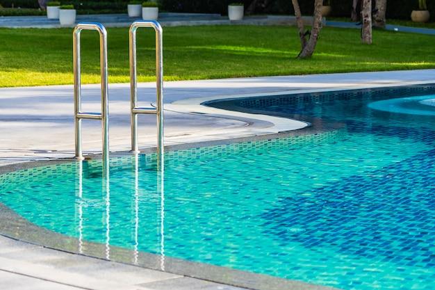 Piękny parasol i krzesło wokół odkrytego basenu w hotelowym kurorcie na wakacje wakacje podróży