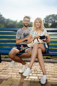 Piękny pary obsiadanie z francuskim buldogiem na ławce w parku