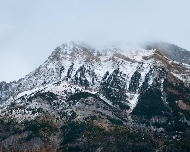 Piękny pasmo wysokich skalistych gór pokrytych śniegiem w ciągu dnia