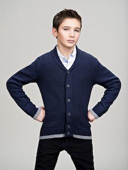 Piękny, pewny siebie nastoletni chłopak pozowanie studio jako modelka.