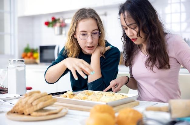 Piękny piekarz robi ciasta, słodkie szczęśliwe dwoje kobiety bawią się w klasie robienia chleba i używają rąk do wspólnego klepania ciasta, aby razem zrobić ciasta w domowej kuchni.