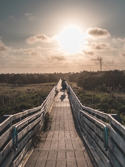 Piękny pionowy symetryczny strzał z drewnianym mostem prowadzącym na plażę, zrobiony o złotej godzinie