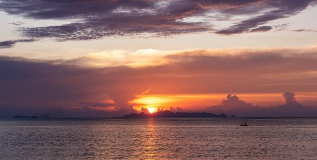 Piękny plażowy zmierzch z błękitnym morzem i złotym lekkim niebem chmurnieje