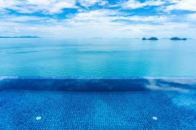 Piękny plenerowy basen z dennym oceanem na białej chmury niebieskim niebie