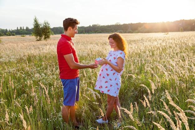 Piękny plenerowy wizerunek młodego mężczyzny dającego prezent swojej ciężarnej żonie. rodzinna sesja zdjęciowa w ciąży w przyrodzie