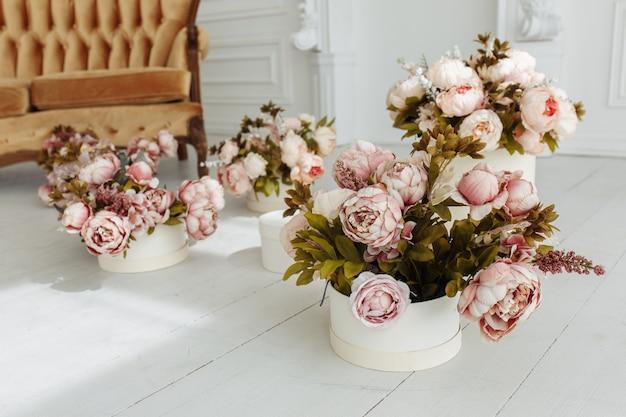 Piękny pokój dzienny provance z brązową sofą w pobliżu kominka z kwiatami i świecami