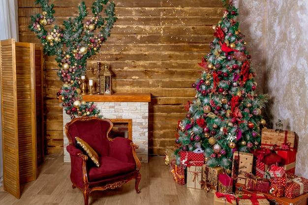 Piękny pokój świąteczny. świąteczny świerk, kominek i fotel w przytulnym pokoju. christmas studio z drewnianymi ścianami i girlandą