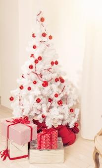 Piękny pokój udekorowany białą choinką z prezentami pod nią.