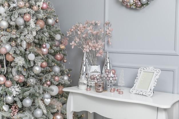Piękny pokój z dekoracjami z choinką i prezentami pod nią. stylowe, świąteczne wnętrze utrzymane w szarej kolorystyce.