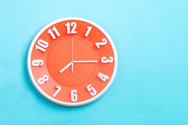 Piękny pomarańczowy zegar ścienny na niebieskim tle