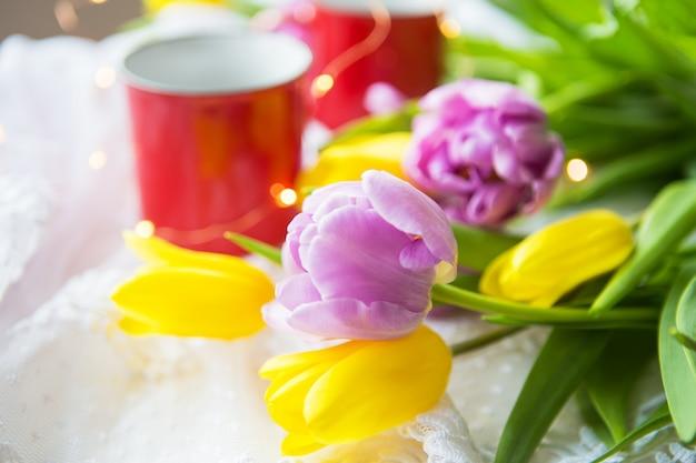 Piękny poranek, dwie filiżanki kawy i bukiet jasnych i pięknych tulipanów.