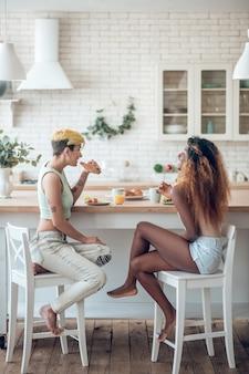 Piękny poranek. młody dorosły, szczupły amerykański i kaukaski dziewczyna boso zrelaksowany, jedzenie, siedząc przy kuchennym stole