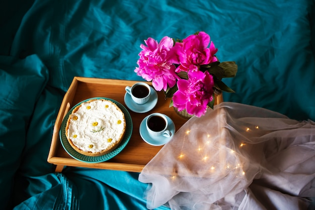 Piękny poranny sernik waniliowy, kawa, niebieskie kubki, różowe piwonie w szklanym wazonie.