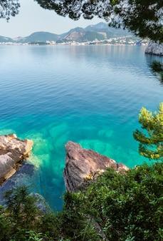 Piękny poranny widok na wybrzeże z zieloną powierzchnią wody i kamienistym wybrzeżem (czarnogóra, budva).