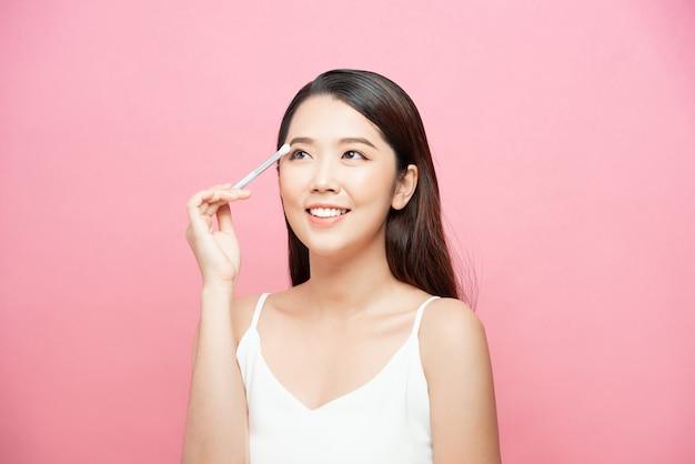 Piękny portret atrakcyjnej młodej kobiety stosującej brązowe cienie do makijażu