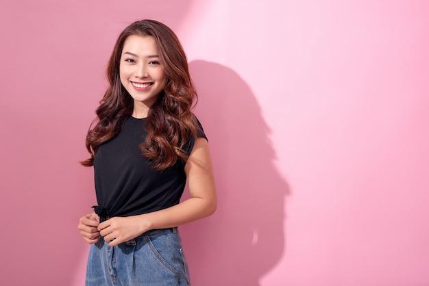Piękny portret azjatycki wesoła młoda dziewczyna pozuje w ubranie z promiennym uśmiechem stojąc na białym tle na różowej ścianie