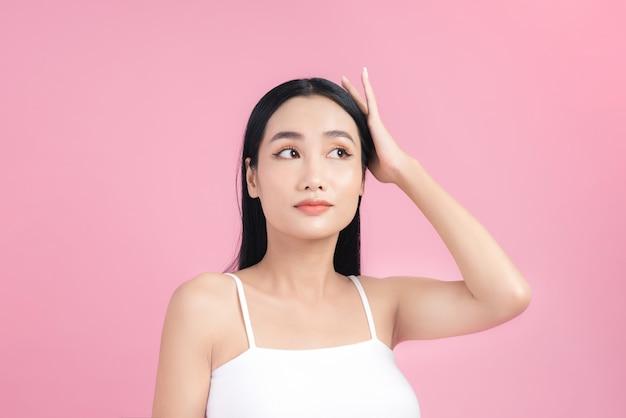Piękny portret azjatyckiej kobiety z długimi zdrowymi, prostymi i lśniącymi włosami